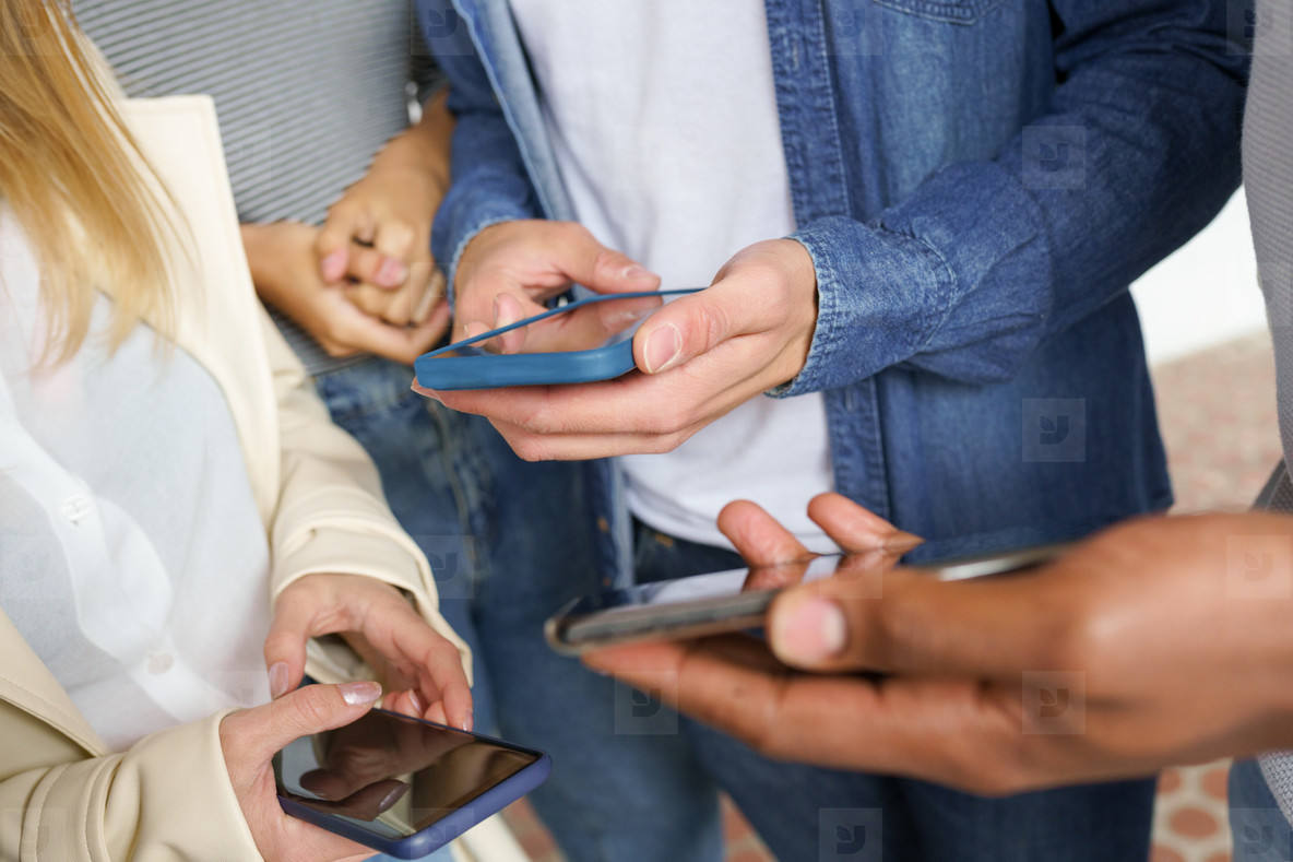 Hands of young unrecognizable people using smartphone