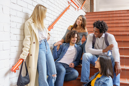 Group of friends with ethnic variety  sitting on some street steps having fun together