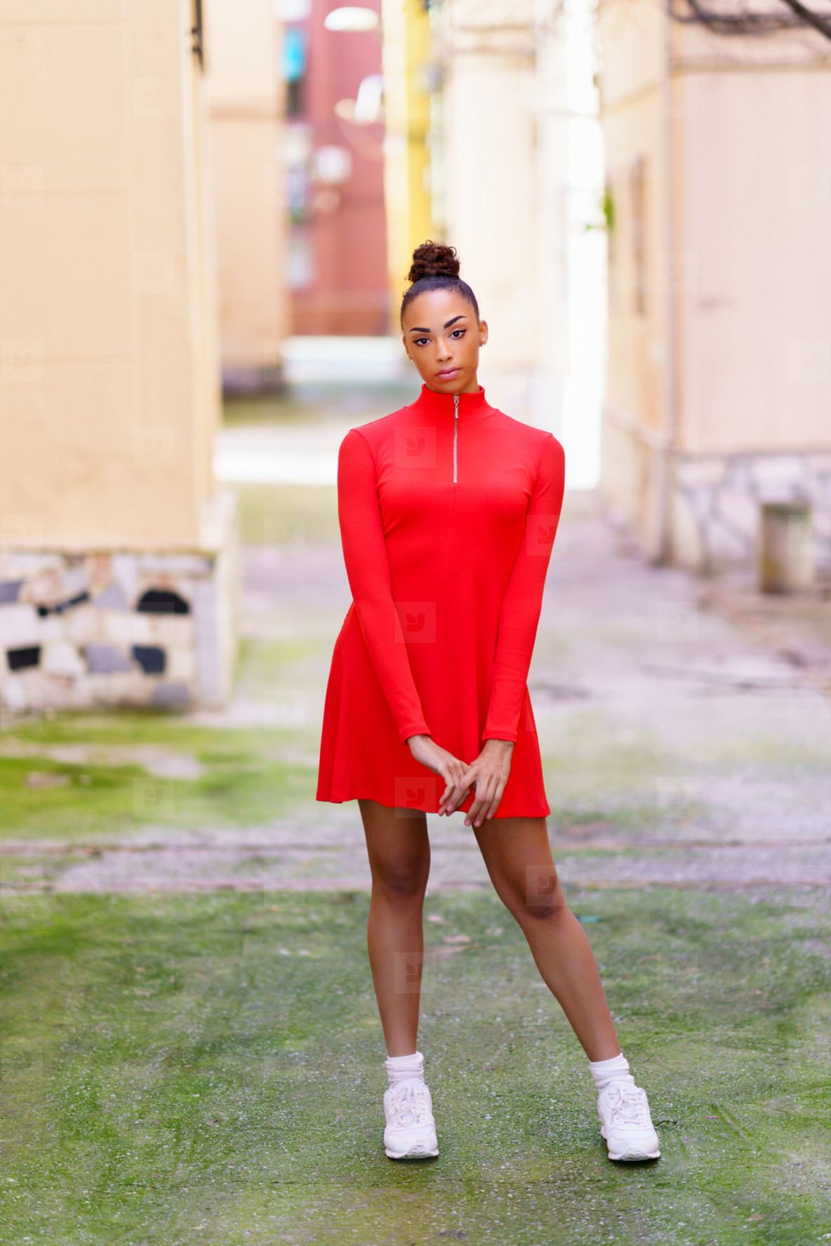 Young black woman in red dress posing on a street with colorful walls