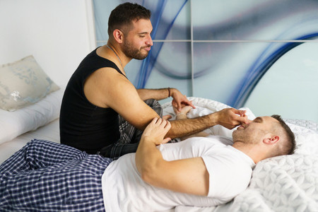 Gay couple talking in a romantic moment on their bed