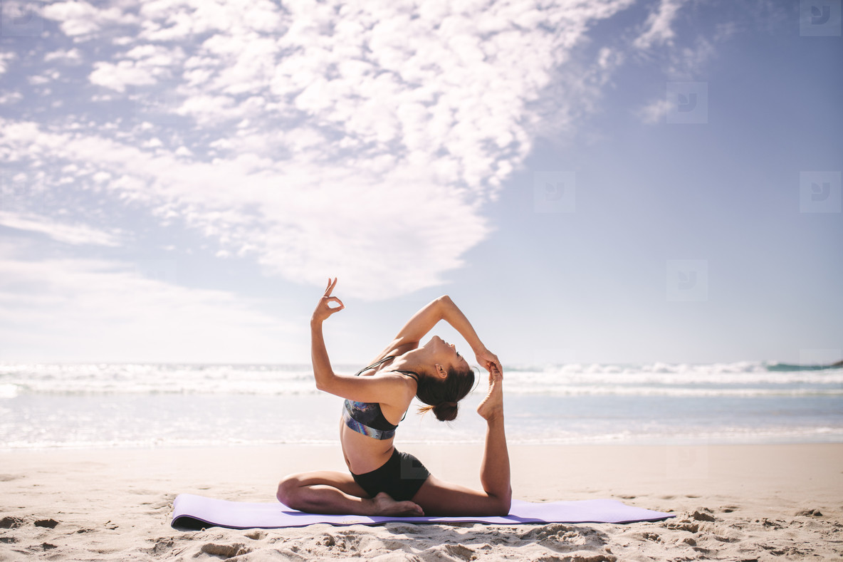 Woman doing one legged king pigeon pose on the beach