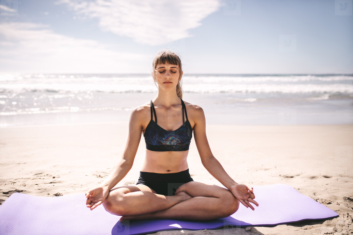 Fit woman meditating on beach
