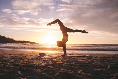 Fitness female practicing yoga at sunset