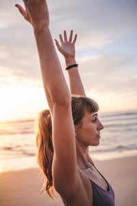 Female doing stretching exercise on the beach