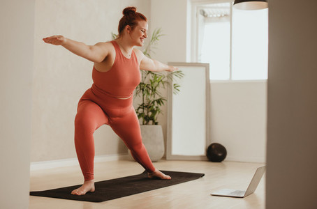 Woman exercising with watching workout class online on laptop