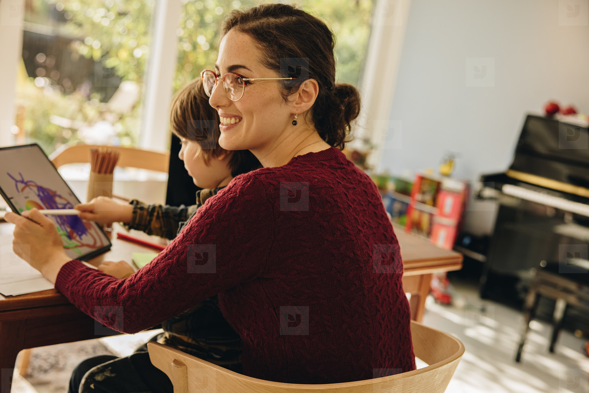 Woman sitting with son drawing