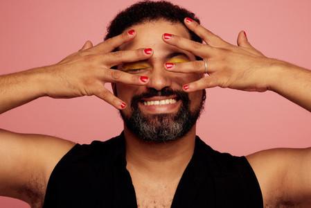 Queer wearing nail polish and eye makeup