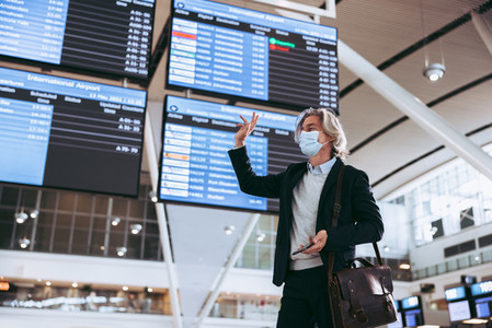 Businessman at airport traveling post pandemic lockdown