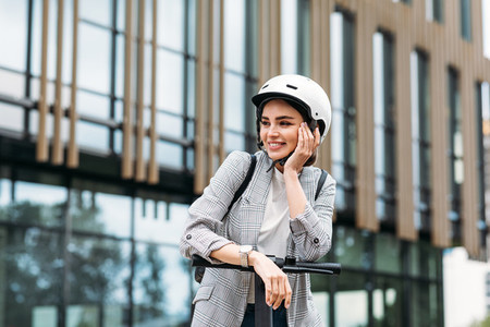 Positive woman leaning on handlebar of electric push scooter  Pretty female in helmet looking away while standing in the city