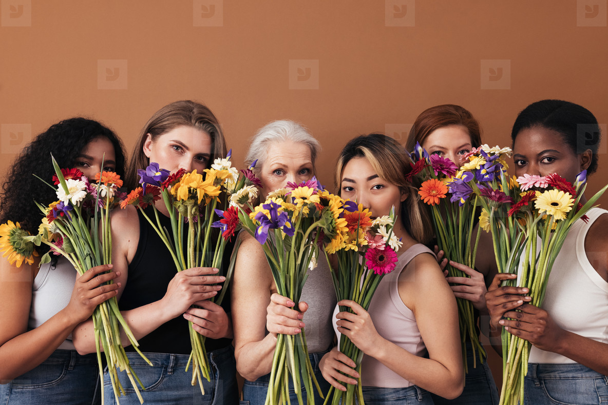 Group of diverse women hide their faces by bouquets of flowers  Portrait of six females of a different race  age  and figure type