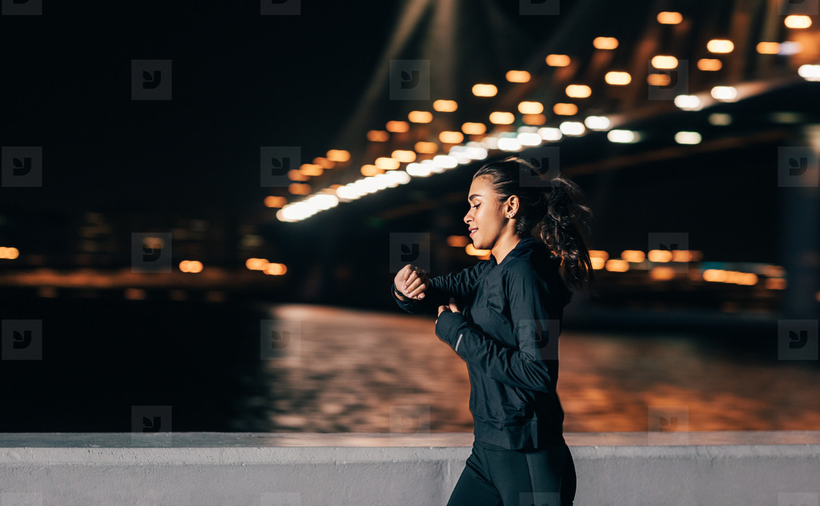 Young middle east woman jogging at night looking in fitness tracker on her wrist