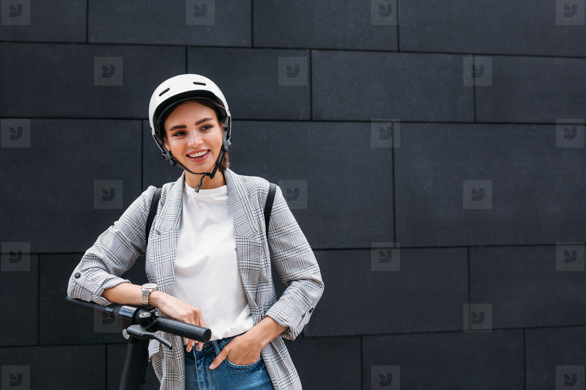 Portrait of a smiling businesswoman leaning on handlebar of electric push scooter  Young cheerful female in cycling helmet at black wall looking away