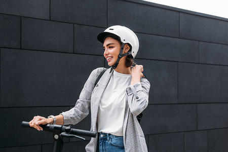 Young happy female adjusting strap of a backpack while standing at wall on electric scooter  Businesswoman with cycling helmet holding handlebar looking away