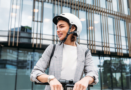 Portrait of a confident businesswoman in safety helmet standing outdoors with electric scooter