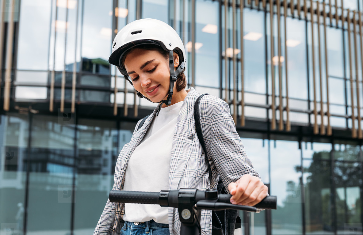 Young woman in helmet holding a handlebar of electric scooter in the city