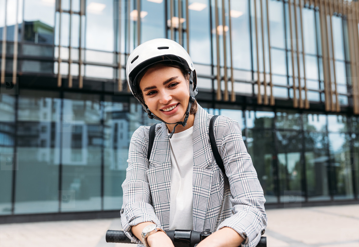 Portrait of a cheerful woman with safety helmet on her head standing against building