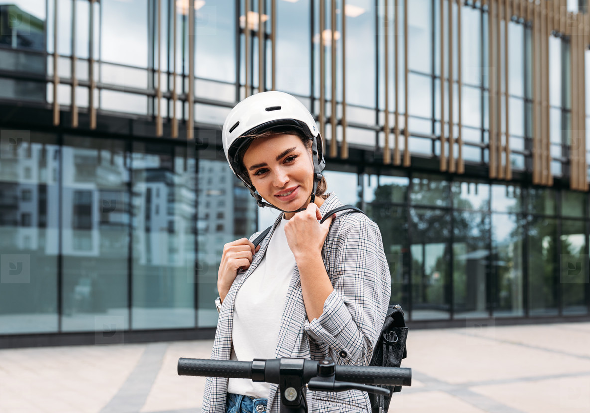 Beautiful caucasian woman in white cycling helmet posing outdoors and looking at camera