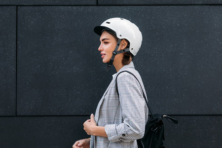 Side view of a good looking businesswoman in cycling helmet standing at black wall in the city