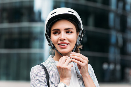 Smiling businesswoman strapping on a cycling helmet while standing in the city  Young female putting a white helmet on her head