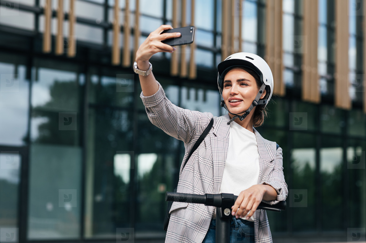 Young beautiful woman in a white cycling helmet taking selfie while standing on an electric push scooter in the city