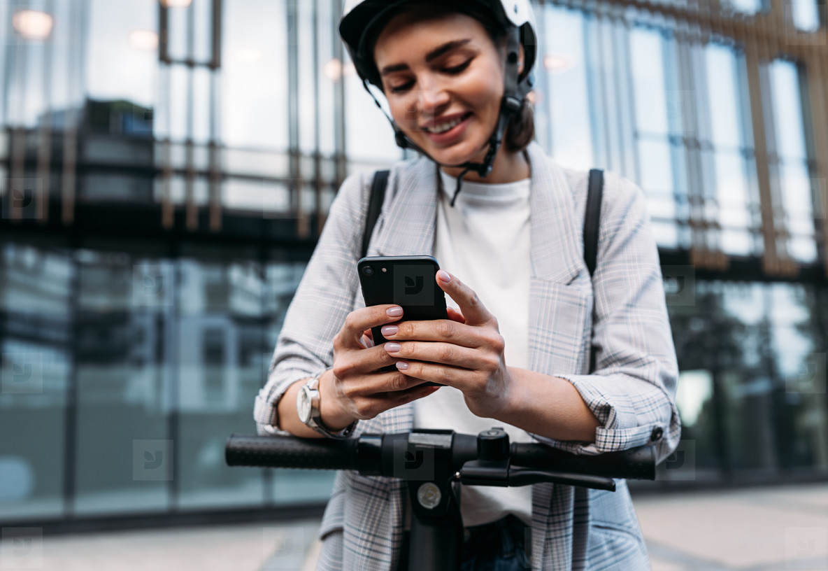 Close up of businesswoman hands holding smartphone while standing on electric scooter