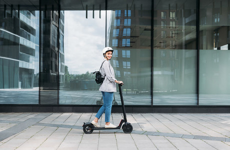 Side view of young smiling businesswoman with cycling helmet on her head driving an electrical push scooter