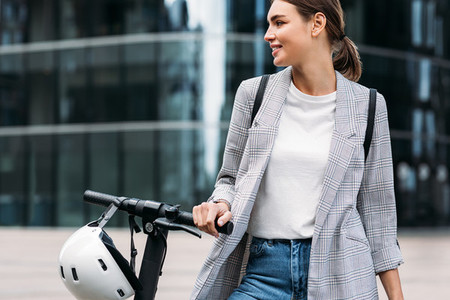 Beautiful caucasian businesswoman in formal wear holding a handlebar of electric scooter while standing against an office building