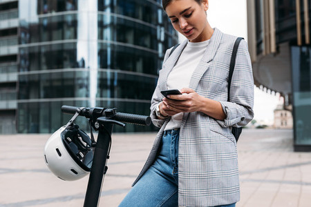 Woman using an app to unlock the electric push scooter  Businesswoman holding smartphone while standing in the city