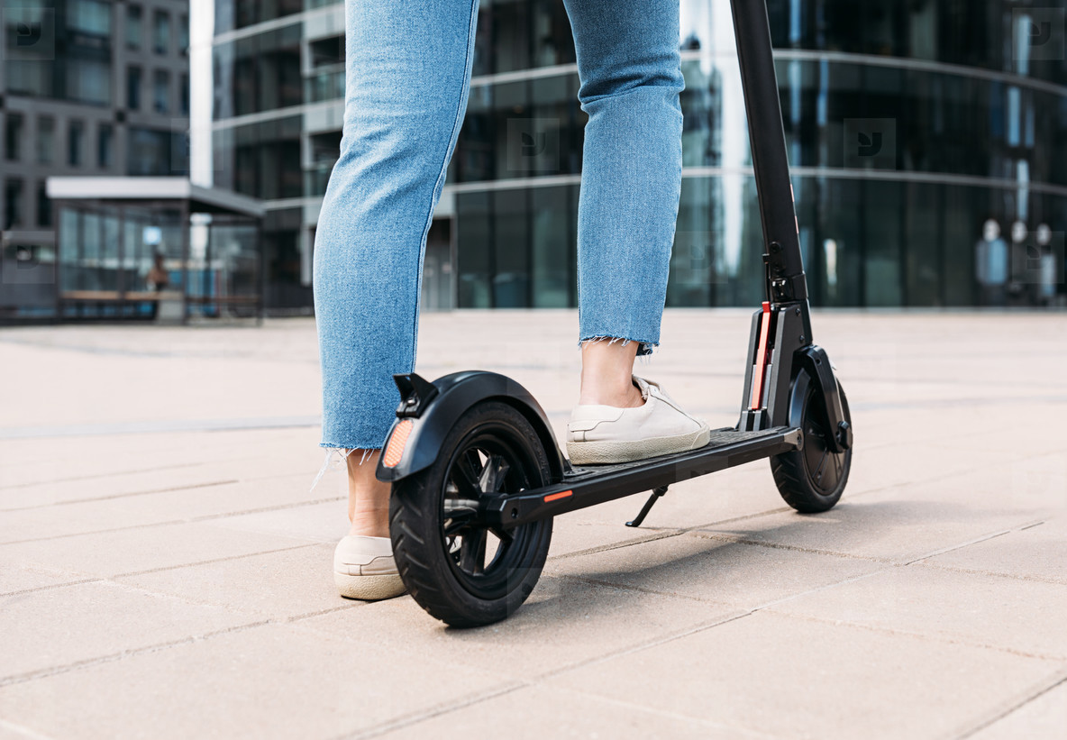 Unrecognizable woman standing on an electric scooter in the city