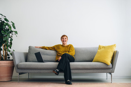 Confident executive sitting on sofa with laptop