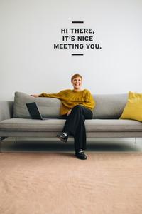 Happy female entrepreneur sitting at lobby