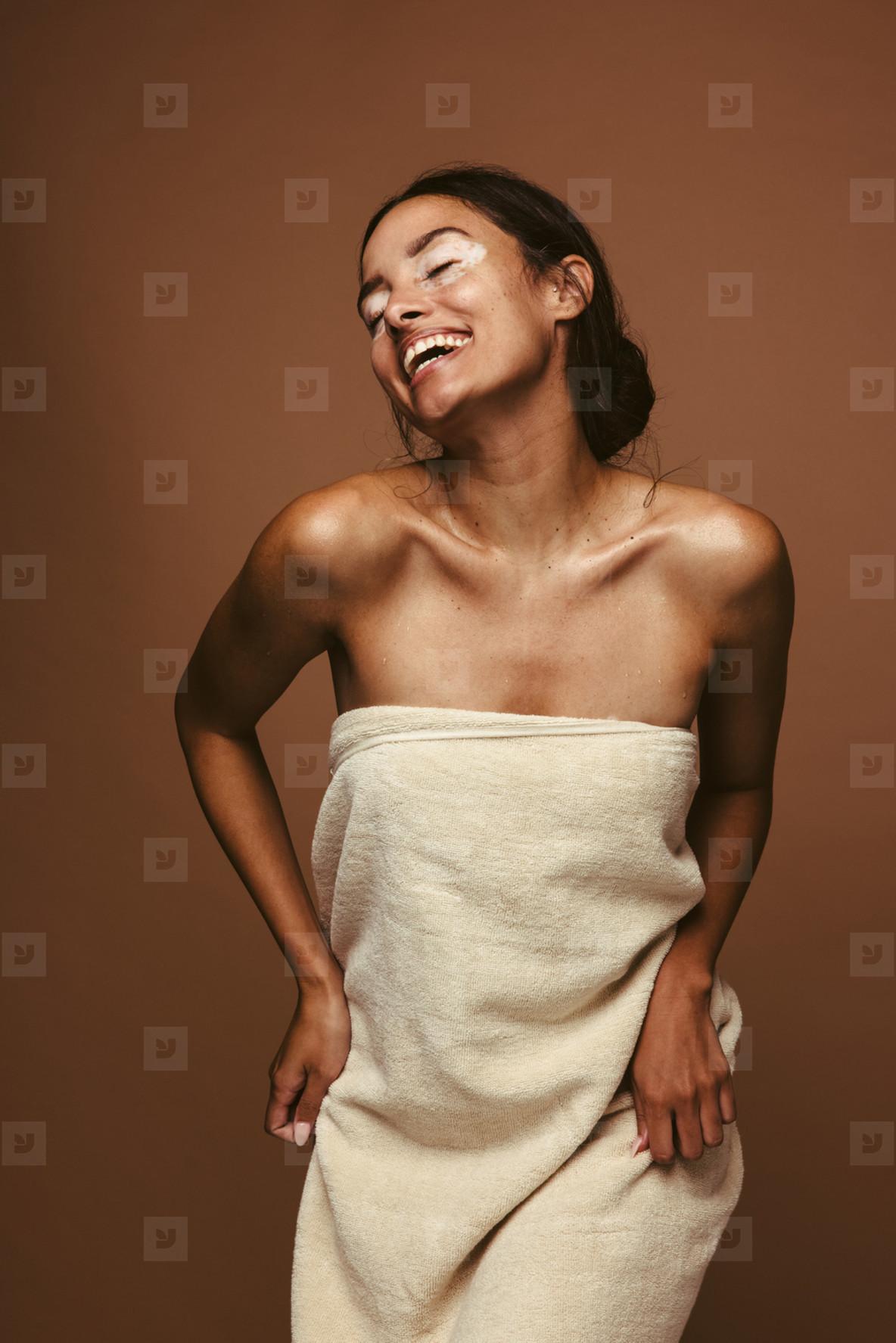 Cheerful woman dancing in bath towel