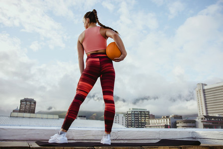 Sportswoman exercising with basketball on rooftop