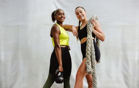 Women with cross training equipment on white background