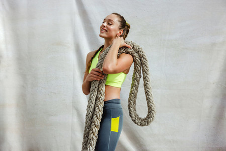 Sportswoman relaxing after battle rope workout