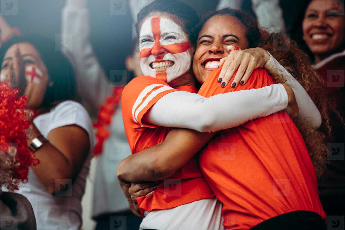 Female soccer fans celebrating a goal at match