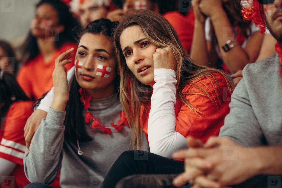 Sad female fans sitting in stadium