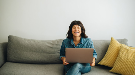 Happy businesswoman with laptop sitting in lobby