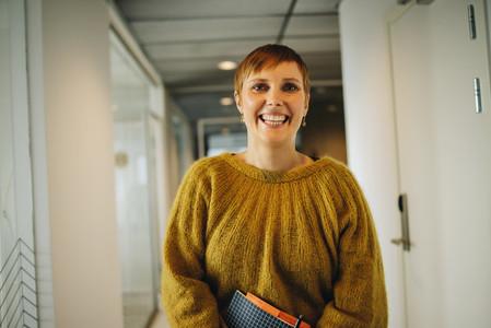 Happy woman standing in office corridor