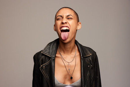 Woman with shaved head sticking out her tongue