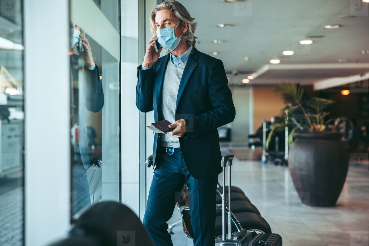 Business traveler waiting for his flight at airport lounge durin