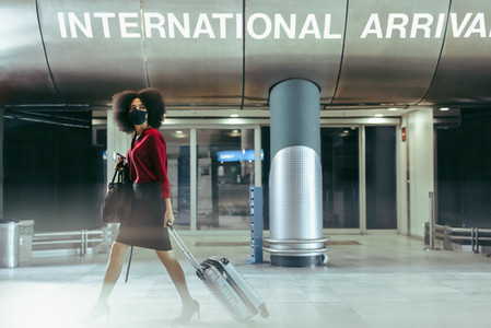 Businesswoman with face mask walking through airport terminal