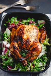 Top view of whole roasted chicken with fresh salad in black dish
