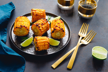 Roasted or grill corn cob with olive oil and salt on a black plate