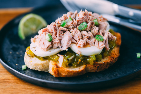 Open sandwich with canned tuna  egg and pickled cucumber dressing served with lime