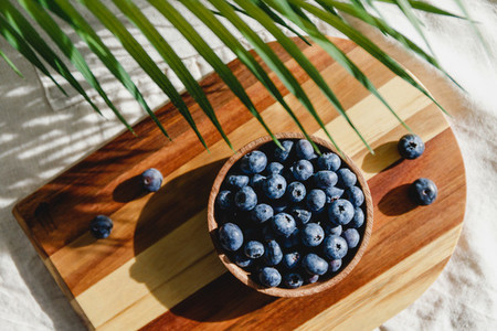 Fresh blueberry in a wooden bowl on a linen light cloth  Healthy eating and Summer concept