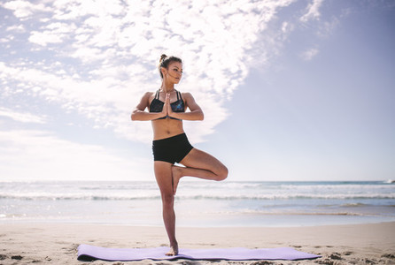 Woman at beach practicing yoga tree position