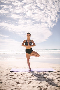 Fitness woman at beach meditating in tree pose yoga