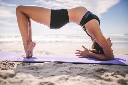Woman doing yoga backbends on the beach