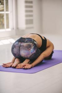 Woman doing yoga in fitness studio